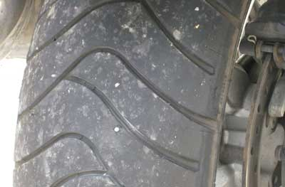 Nail in motorcycle tire, shown flush with tread on rear tire.